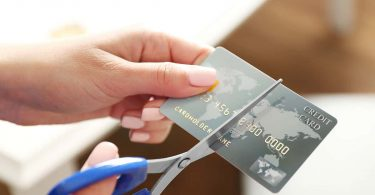 Female hands cutting credit card with scissors