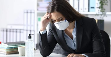 Worried bookkeeper with protective mask looking at calculator on a desk at the office