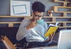 Young man reading a book in office