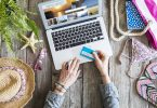 Woman's hands holding credit card in front of laptop